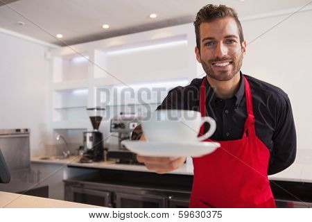Happy barista offering cup of coffee to camera in a cafe
