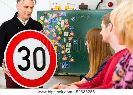 Driving school - driving instructor and student drivers with a tempo thirty Road sign, in the background are traffic signs