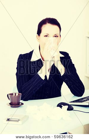 Sick young business woman blowing her nose.