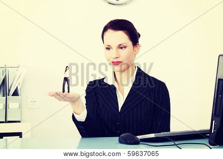 Businesswoman holding a miniature of worker on her hand that she choosed of all applicants.