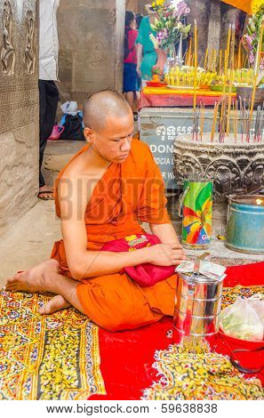 SIEM REAP, CAMBODIA - DECEMBER 28, 2012: buddhist monk is sitting by figure of Vishnu with eight arms in Angkor Wat temple