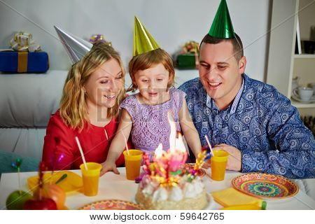 Family of three sits at birthday table, daughter prepares to snuff out candle on cake and parents look at her