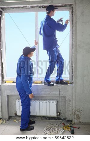 Two men in working clothes set new window frame, one of them standing on the windowsill and fastens frame