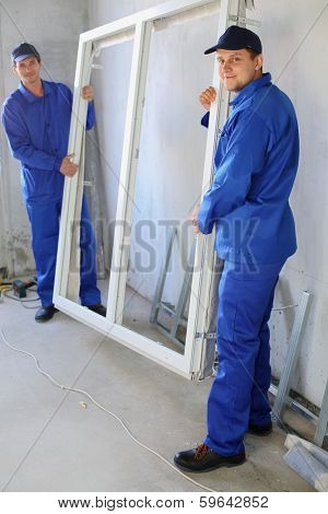 Two men in work clothes holding new window frame in a room under renovation