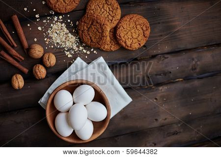 Several eggs in bowl with walnuts, cinnamon and bisquits near by