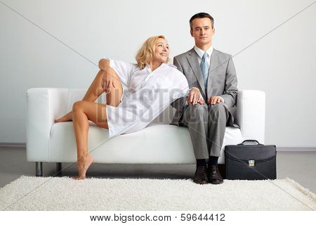 Photo of serious man in suit sitting on sofa with seductive happy woman near by