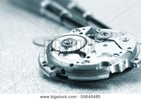 Extreme close up shot of broken watch mechanism and repair tools.