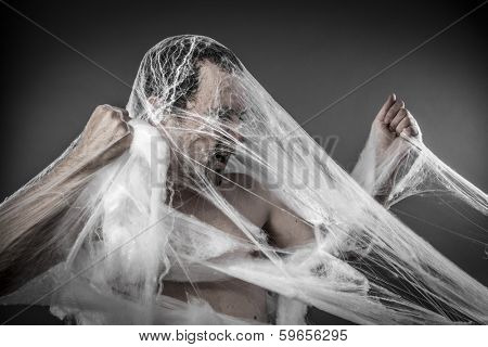 Danger. man tangled in huge white spider web