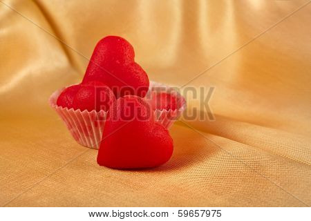 Sweet Red Marzipan heart candy on golden silk cloth surface background