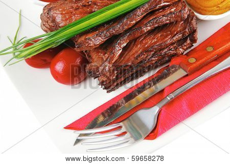 roast red beef meat fillet with red hot pepper with ketchup mayonnaise and mustard on plate isolated on white background