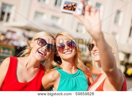 holidays and tourism, modern technology concept - beautiful girls taking picture with digital camera in the city