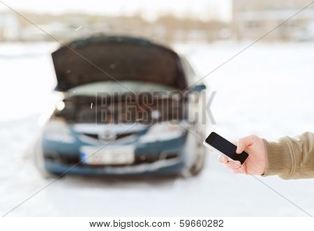 transportation, winter and vehicle concept - closeup of man with broken car and smartphone
