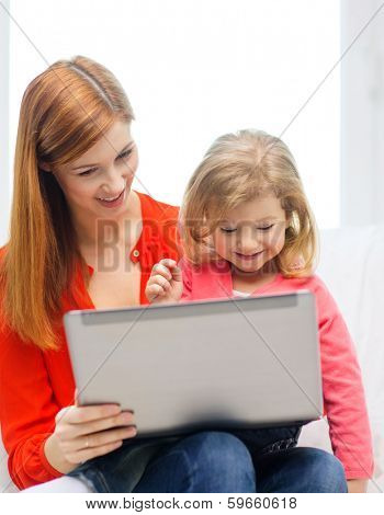 family, children, parenthood, technology and internet concept - happy mother and daughter with laptop computer at home