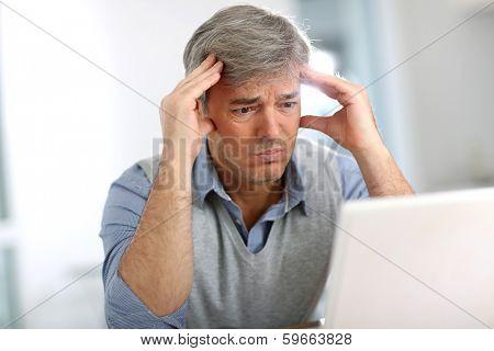 Senior businessman in front of laptop having a headache