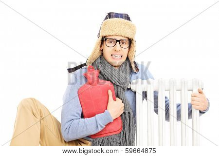 Chilled young man with hot water bottle hugging a radiator isolated on white background