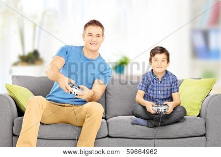 Young man playing video game with his younger cousin, at home