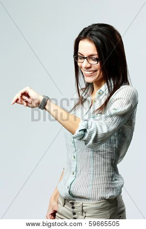 Young happy businesswoman looking at her watch on wrist on gray background