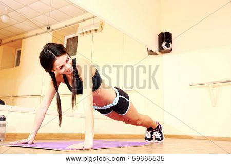 Young happy fit woman doing pushups at gym