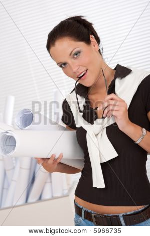 Smiling Female Architect Holding Plans And Glasses