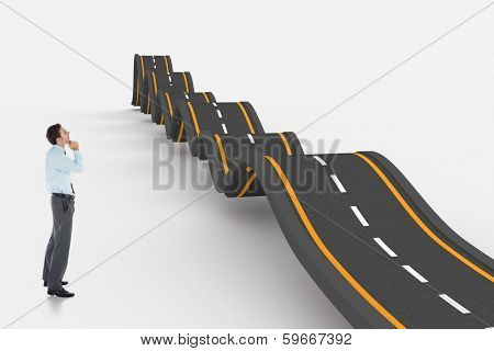 Thoughtful businessman with hand on chin against bumpy road background