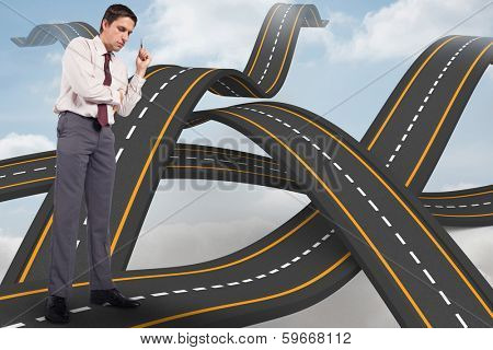 Thinking businessman holding pen against bumpy roads crossing backdrop