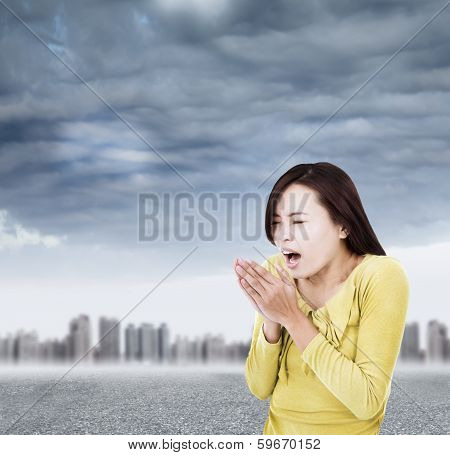 Young Woman Blowing To Warm Hands Up With Black Clouds
