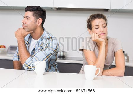Unhappy couple having coffee not talking at home in kitchen