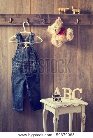 Little boy's bedroom with pair of dungarees and teddy bear hanging from hooks - vintage toned effect