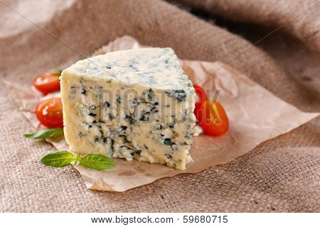 Tasty blue cheese with tomatoes and basil, on burlap background