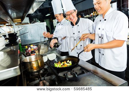 Asian Chefs in Hotel or Restaurant Kitchen cooking and finishing dishes