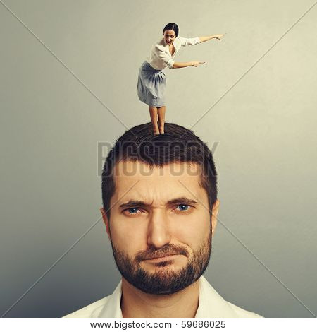 small woman standing on the head of displeased man and showing the direction
