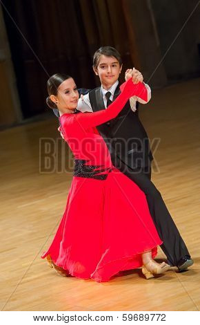 Couple of kids waltzing at dance competition