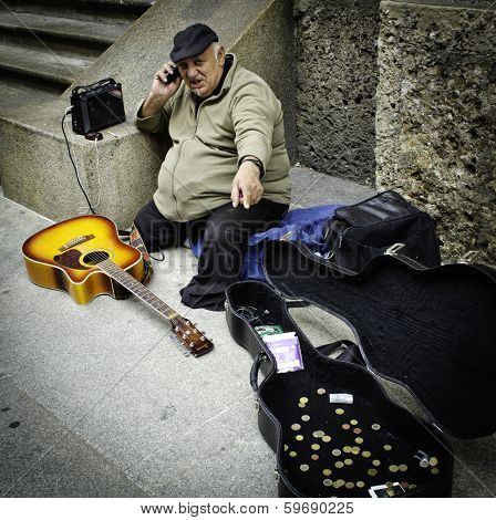 MILAN, ITALY - MAY 04, 2012: Elderly beggar musician with guitar ask for money on street of Milan/
