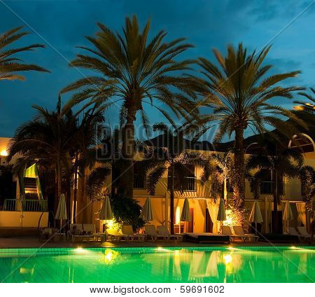 Night swimming pool against the backdrop of palm trees and hotels