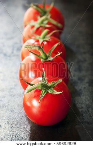 Row of truss tomatoes on dark slate.