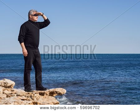Mature Businessman Standing Lookout On A Rock