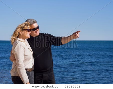 Affectionate Mature Couple At The Seaside Pointing Copyspace