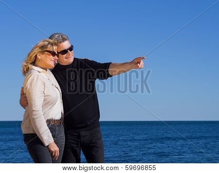 Romantic Mature Couple Pointing To Copyspace At The Coast