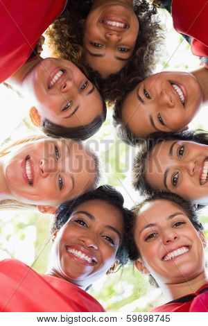 Directly below shot of happy female soccer team forming huddle