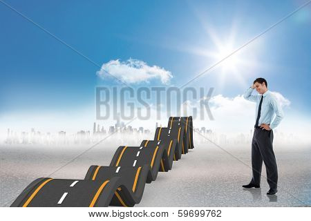 Thoughtful businessman with hand on head against bumpy road leading to city