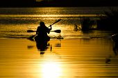 stock photo of kayak  - Sunset lighting silhouetes of men kayaking in the lake - JPG