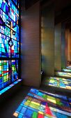 image of church interior  - Church interior with modern stained glass windows making colorful reflections on walls and floor - JPG