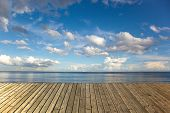pic of dock a lake  - Empty wooden pier on a sea with blue sky and clouds - JPG