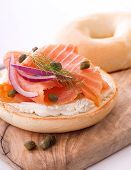 stock photo of bagel  - A delicious bagel with smoked salmon lox cream cheese red onion capers and a sprig of dill - JPG