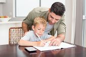 picture of homework  - Happy father helping son with math homework at table at home in kitchen - JPG