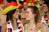 German girls friends soccer fans celebrating victory.