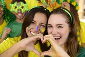 stock photo of enthusiastic  - Cheerful couple of Australian or Brazilian or Cameroonian girlfriends soccer fans - JPG