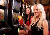 stock photo of gambler  - Friends in Casino on a slot machine - JPG