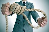 stock photo of hangmans noose  - man wearing a suit holding a rope with a hangmans noose - JPG