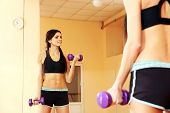 Young smiling fit woman doing exercises with dumbells and looking at her reflection at gym